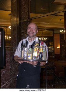 madrid-waiter-carrying-a-tray-of-drinks-bottles-and-glasses-b5p7yg